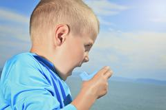 Young sport boy using inhaler outside Stock Photos