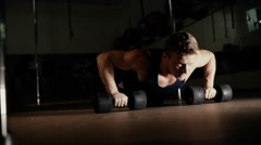 Athletic man doing push ups from dumbbells in gym Stock Footage