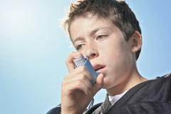 Teen having a asthma problem with sky on the background Stock Photos