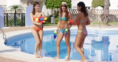 Three sexy young women playing with water guns Stock Footage