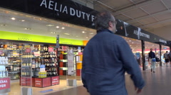 Travellers shopping in duty free aera - Beauvais airport, France - Zoom out Stock Footage
