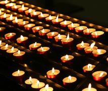 Series of candles lit with flickering flame in the place of prayer Stock Photos