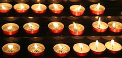 Many candles lit inside the place of worship to pray Stock Photos