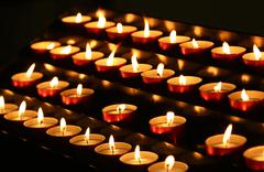 Many candles lit with flickering flame in the sanctuary Stock Photos