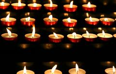 Series of candles lit inside the place of worship to pray Stock Photos