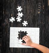 Hands starting to collect puzzle pieces Stock Photos