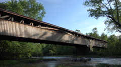 4K Long Historic Wooden Covered Bridge Stretches Over Running Stream Stock Footage