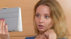 Blonde talking by skype, showing thumb, smiling, close up Stock Footage