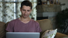 Man having a video chat greeting with interlocutor sitting on the couch Stock Footage