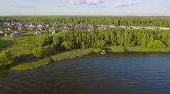 Aerial countryside landscape, fields forest and village with cozy houses on lake Stock Footage
