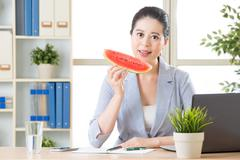 confidence asian business woman leader having sweet watermelon to reduce temp - stock photo