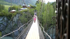 People crossing suspension bridge Stock Footage