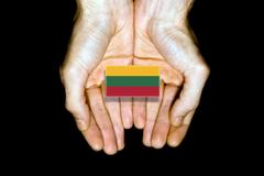Flag of Lithuania in hands on black background Stock Photos