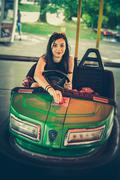 Young woman having fun in electric bumper car Stock Photos