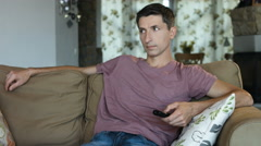 Handsome man changing TV channels with remote control sitting on sofa at home Stock Footage