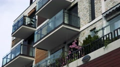 6.Part of modern multi-storey house with windows and flower on balconies Stock Footage