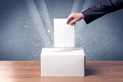 Ballot box with person casting vote - stock photo