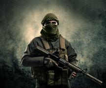 Portrait of a heavily armed masked soldier with grungy background - stock photo