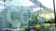 Chairs and tables under the sunshades - view across window Stock Footage