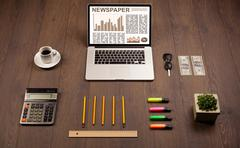 Business laptop with stock market report on wooden desk - stock photo