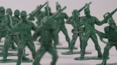 Symbolic toy soldiers falling down - dying, death and sacrifice - stock footage