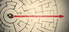 Business person standing in the middle of a circular maze - stock photo