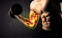 Bodybuilder athlete lifting weight with fire explode arm concept - stock photo