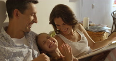 Mother, father and daughter wearing pajamas reading a book together laying  Stock Footage