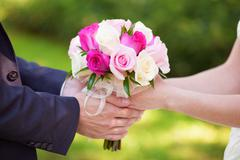 Bride and groom holding colourful wedding bouquet. Marriage concept Stock Photos