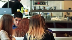 Customers sit at the table and cooks prepare a food behind bar in restaurant Stock Footage