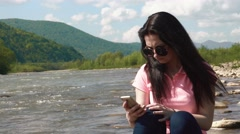 Young displeased brunette woman sending sms on smartphone while relaxing at the Stock Footage