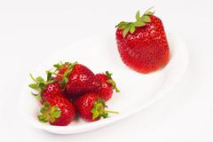 Organic strawberries and a big GMO strawberry are on white plate on white backgr Stock Photos