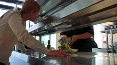 Cooks in kitchen prepare a food and waitress speaks with them Stock Footage