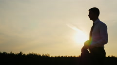 Young businessman looking confidently ahead. It should be at sunset. Concept Stock Footage