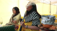 Two women sit at table, smoke a hookah and drink wine Stock Footage