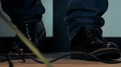 Man stands and tap his feet to rhythm - detail of legs Stock Footage