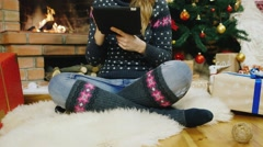 Young beautiful woman sitting by the fireplace, enjoy the tablet. Christmas Stock Footage
