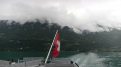 Switzerland Flag Waves On Lake with Swiss Alps Stock Footage