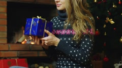 An attractive woman with a gift in their hands. Sitting by the fireplace with - stock footage
