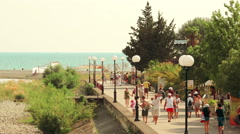 Street of a small resort town near the sea filled with strolling tourists Stock Footage