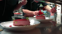 Two plates with cakes are prepare on table in kitchen and waiter takes it away Stock Footage