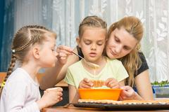 Mother and two children baking pour the mass into molds preparing muffins for - stock photo