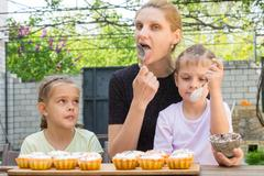 Mother and two daughters lick spoons with confectionery icing for Easter cupc - stock photo