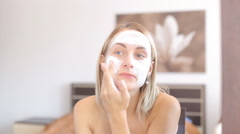 Female beauty, happy mid adult woman putting cream on face skin and smiling - stock footage