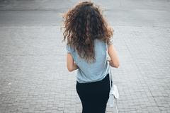 Slender young girl with magnificent curly hair in a skirt and with handbag wa - stock photo