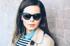Portrait of a young beautiful brunette woman in sun glasses and a coat outdoo Stock Photos