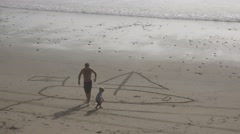A father and children draw a sailboat in the sand on a beach. Stock Footage