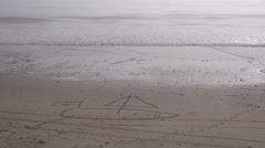 A sailboat is drawn in the sand on a beach. Stock Footage