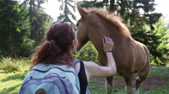 Woman traveler in the mountains playing with foal Stock Footage