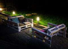 Night garden with self-made couch from pallets is illuminated garden lamps Stock Photos